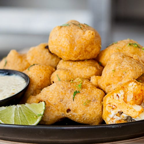 Spicy Buffalo Battered Roasted Cauliflower with Garlic Confit and Oregano Lime Cream Dip